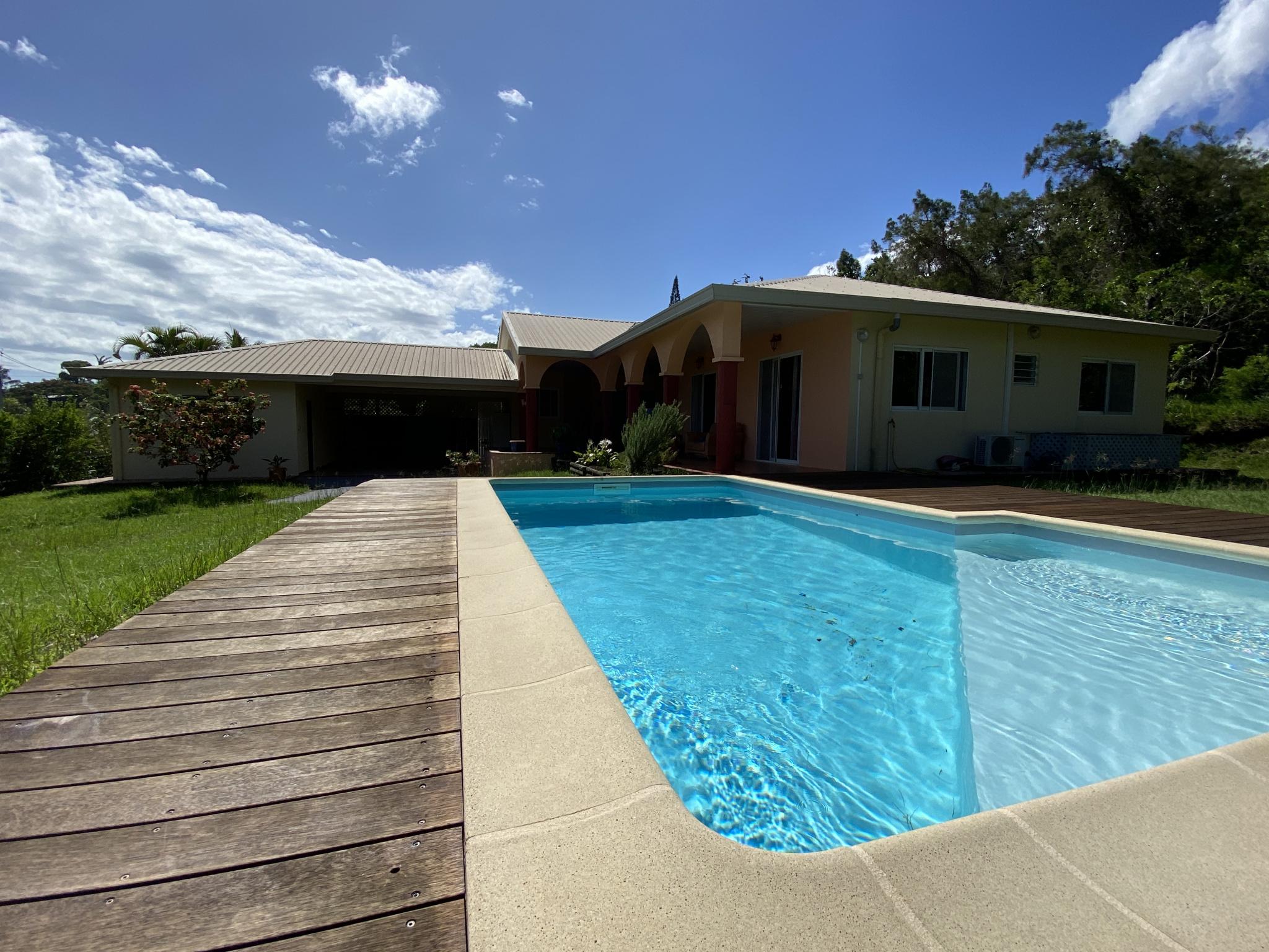 Vue piscine et maison en arrière plan
