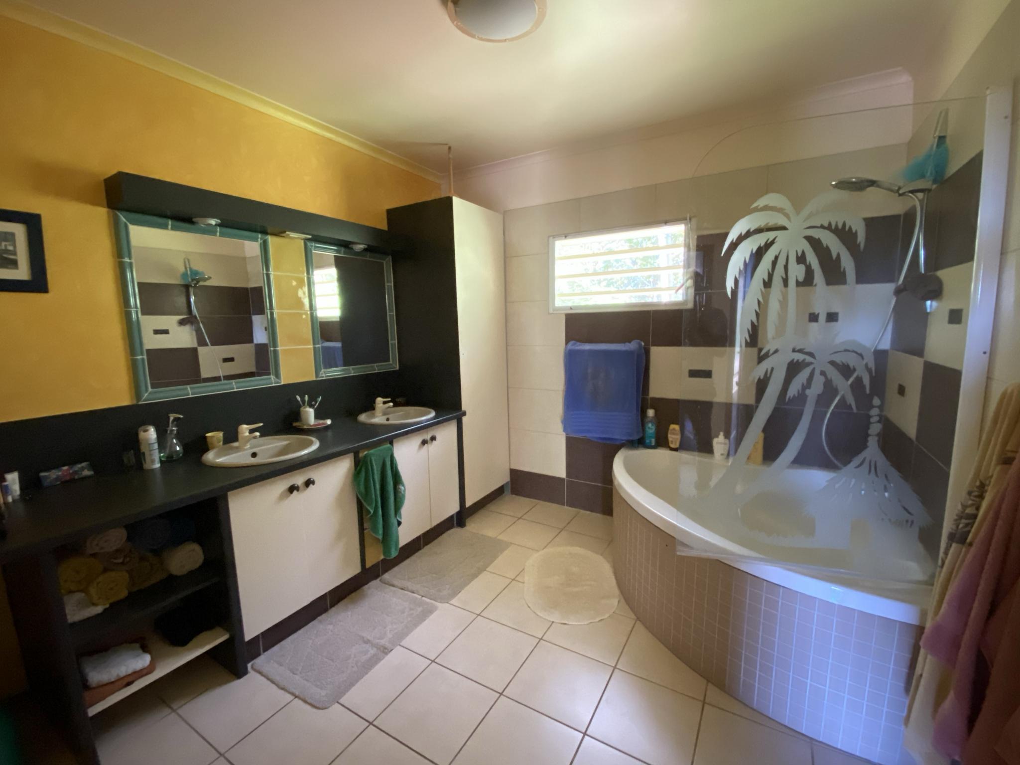 Grande salle de bain avec baignoire en coin