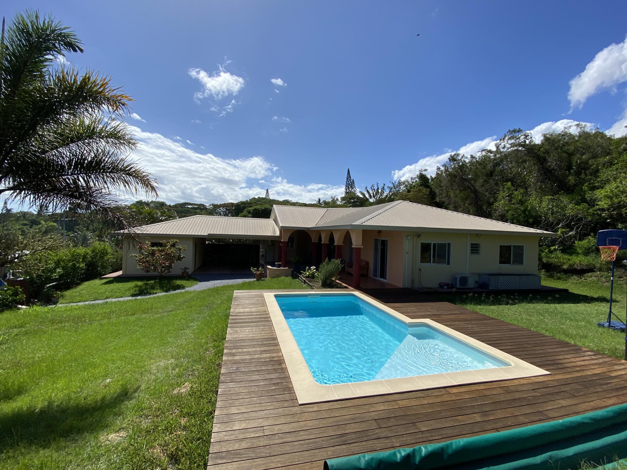 Vue avec piscine, jardin bien entretenu et maison en arrière plan